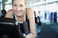 Young woman on exercise bike, smiling, close up, portrait