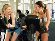 Two young women on exercise bikes, smiling