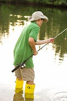 Side profile of a teenage boy holding a fishing rod