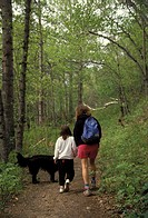 Woman and child hiking in the woods with a dog. The child is wearing protective clothing. The woman in shorts is more susceptible to mosquito and tick...