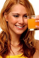 A woman looking at a glass of orange juice