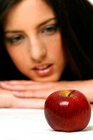 A woman resting her chin on her hands while looking at a red apple