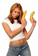 A woman in white shirt and jeans holding up two bananas like holding two guns
