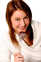 A woman holding up a fork of chocolate ball cake