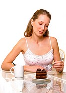 A woman looking and holding a fork with a plate of chocolate cake and a cup of water on the table