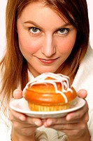 An up-close picture of a woman holding up a plate of pastry