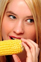 A woman biting a maize
