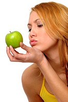 A woman trying to kiss a green apple