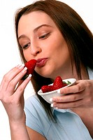 A woman kissing a strawberry while holding another bowl of strawberries