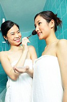 Two asian women in towels with one helping the other to put on blusher