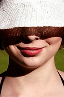A woman wearing a hat covering half of her face