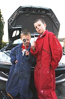 Two boys disguising as mechanics holding repairing tools and standing in front of a car