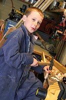 A boy disguising as a carpenter hammering a nail in a workshop