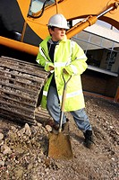 A boy in protection suit holding a spade while leaning against an excavator