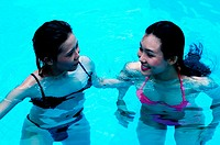 Two friends having fun swimming in the pool