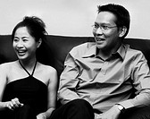 A man and a woman sitting on the couch smiling (thumbnail)