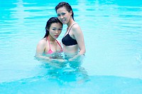 Two women posing in the pool