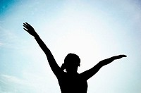 Silhouette of woman spreading her hands (thumbnail)