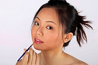 Woman applying some colours on her lips (thumbnail)