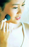 Woman brushing some blusher on her cheek (thumbnail)