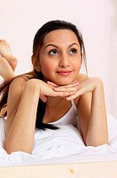 Woman lying forward on the bed daydreaming