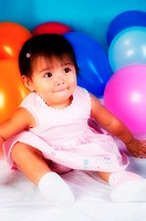 Baby girl sitting with balloons