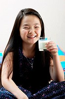 Girl holding a glass of milk.
