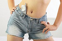 Woman keeping her mobile phone in her denim shorts