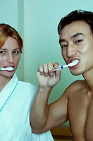 Couple brushing teeth together