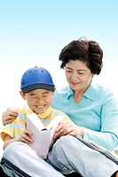 Woman and her grandson reading book together