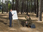 Businessmen holding meeting in forest