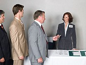 Businesswoman giving out name tags