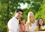 Family sitting at table with juice, outdoors
