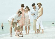 Group standing on the beach, man bending over to talk to daughter