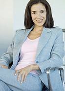 Businesswoman sitting in chair, smiling at camera, portrait