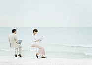 Businesspeople sitting on stools on beach, one using laptop, another reading newspaper
