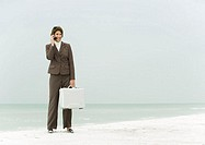 Businesswoman standing on beach holding briefcase, using cell phone