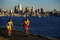 Pair rollerblading, city and lake backdrop, Gasworks Park, Seattle, Washington, USA