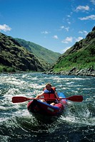 Woman navigates inflatable kayak through Snake River, Idaho, USA, elevated view
