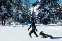 Woman walking through snow with dog