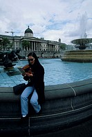 Woman sitting at fountain in Trafalgar Square reading guidebook, London, England