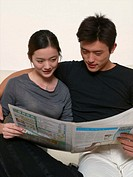 Young couple on sofa reading newspaper together