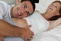Man lying on bed with head resting against pregnant woman´s bump