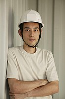 Young man wearing helmet, arms crossed, portrait