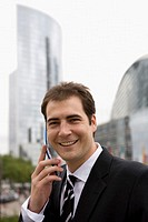 Businessman talking on mobile phone, smiling, portrait