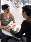Couple sitting in cafe holding hands, smiling