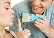 Woman holding up finger in front of paintbrush held by man