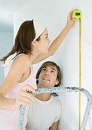 Woman on ladder using measuring tape as man watches (thumbnail)