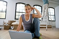 Woman sitting on floor by laptop, man on ladder in background