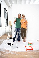Couple standing by wall holding paint roller and brush, portrait